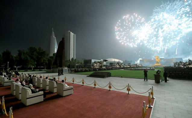 "Senior DPRK officials and invited foreign guests watch the fireworks display ""We will always emerge victorious!"" from an outdoor venue near the Victorious Fatherland Liberation War (Korean War) monuments in Po'tonggang District in central Pyongyang on 27 July 2013.  Visible in the background L is the Ryugyo'ng Hotel and an apartment tower for senior DPRK Cabinet officials (Photo: Rodong Sinmun)."