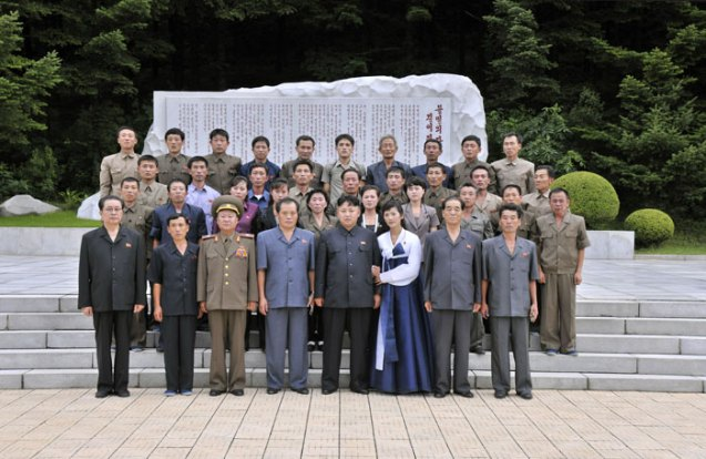 Kim Jong Un (5th L) poses for a commemorative photograph in front of a monument at Songhung Revolutionary Site on 29 July 2013