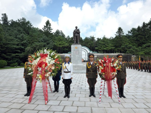 A KPA honor guard stand beside a floral wreath from Kim Jong Un (L) and the Party Central Military Commission (R) at the CPV Martyrs' Cemetery in Hoech'ang County, South P'yo'ngan on 29 July 2013 (Photo: Rodong Sinmun).