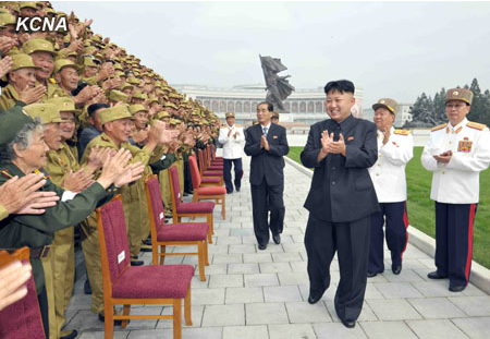 Kim Jong Un (3rd R) applauds during a commemorative photo session with veterans at the Victorious Fatherland Liberation War (Korean War) Museum in Pyongyang on 30 July 2013 (Photo: KCNA).
