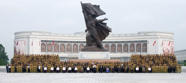 """Kim Jong Un and senior DPRK officials pose for a commemorative photograph with veterans of the Fatherland Liberation War (Korean War) in front of the """"Victory"""" statue and the renovated Victorious Fatherland Liberation War Museum in Pyongyang on 30 July 2013 (Photo: Rodong Sinmun)."""