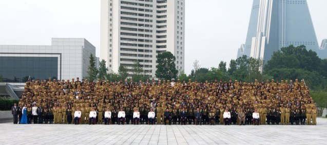 Kim Jong Un and senior DPRK officials poses for a commemorative photograph with veterans of the Fatherland Liberation War (Korean War) in Pyongyang on 30 July 2013.  Seen in the background are the Mirae Shop (L) an apartment building for senior DPRK Cabinet officials (C) and the Ryugyo'ng Hotel (R) (Photo: Rodong Sinmun).