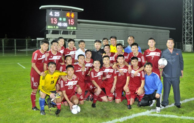 Kim Jong Un poses for a commemorative photograph with the players and coaches of the Hwaebul men's football (soccer) team after their victory over the 25 April men's team.  Also in the photo, R, is KIS Socialist  Youth League Central Committee Chairman Jon Yong Nam, holding the game ball (Photo: Rodong Sinmun).
