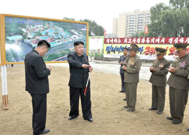 Kim Jong Un (2nd L) issues instructions about the construction of the Munsu Wading Pool in Pyongyang.  Also seen in attendance is architect and leading construction manager, KWP Department Deputy Director Ma Won Chun (L) (Photo: Rodong Sinmun).