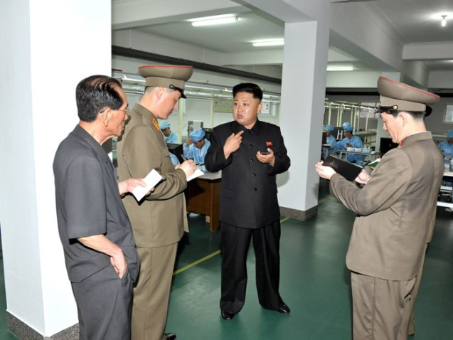 """Kim Jong Un gives instructions on production at the 11 May Factory, after viewing the """"Arirang"""" model handheld 'phone.  Seen in attendance is Ri Jae Il (L), a KWP senior deputy department director and close aide to Kim Jong Un (Photo: Rodong Sinmun)."""