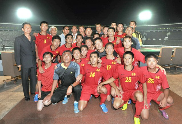 Kim Jong Un poses for a commemorative photograph with members and coaches of the Sonbong Team of the Worker Peasant Red Guards), who won the soccer (football) match.  Also seen in attendance (standing, L) is Col. Gen. O Il Jong, Director of the KWP Military Affairs Department (Photo: Rodong Sinmun).