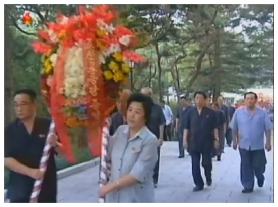 Han Kwang Bok (R), Director of the KWP Science Education Department carries a floral wreath on behalf of the Party Central Committee to the grave of Kim Po Hyon in Pyongyang on 19 August 2013 (Photo: KCTV screengrab).