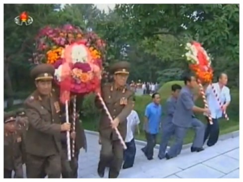 VMar Kim Jong Gak (L) carries a floral wreath to the grave of Kim Po Hyon in Pyongyang on 19 August 2013 (Photo: KCNA).