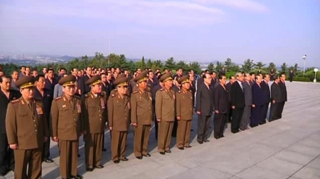 Members of the DPRK central leadership visit Kim Jong Suk's memorial bust at Revolutionary Martyrs Cemetery in Pyongyang to mark her death anniversary on 22 September 2013.  Among those in attendance are: Gen. Kim Won Hong (L), Gen. O Kuk Ryol (2nd L), VMar Ri Yong Mu (3rd L), VMar Kim Yong Chun (4th L), Gen. Jang Jong Nam (5th L), Gen. Ri Yong Gil (6th L), VMar Choe Ryong Hae (7th L), Kim Yong Nam (8th L), Pak Pong Ju (9th L), Kim Ki Nam (10th L),  Choe Tae Bok (11th L), Pak To Chun (12th L) and Yang Hyong Sop (13th L) (Photo: KCNA screengrab).