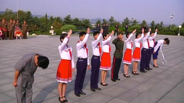 Members of the Kim Il Sung Socialist Youth League and Young Red Guards salute Kim Jong Suk's memorial bust in Pyongyang on 22 September 2013 (Photo: KCNA screengrab).
