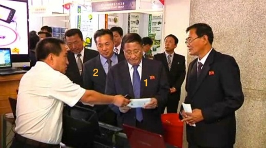 DPRK Vice Premier Kang Sok Ju (1) and Minister of Foreign Trade Ri Ryong Nam (2) visit a company booth at the 9th Pyongyang Autumn International Trade Fair on 23 September 2013 (Photo: KCNA screengrab).