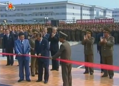Pak Pong Ju cuts a ceremonial tape opening the U'nha Scientists Stree in Pyongyang (Photo: KCTV screengrab).