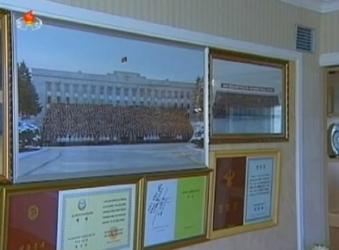 A copy of a December 2012 commemorative photograph (L) of members of the DPRK leadership and personnel involved in the 12 December 2012 launch of the U'nha-3, seen in a resident of the U'nha Scientists' Street (Photo: KCTV screengrab).