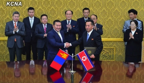 Mongolian Minister of Industry and Agriculture Khaltmaa Battulga (L) shakes hands with DPRK Minister of Foreign Trade Ri Ryong Nam (R) after signing an economic cooperation agreement at Mansudae Assembly Hall in Pyongyang on 28 October 2013 (Photo: KCNA).