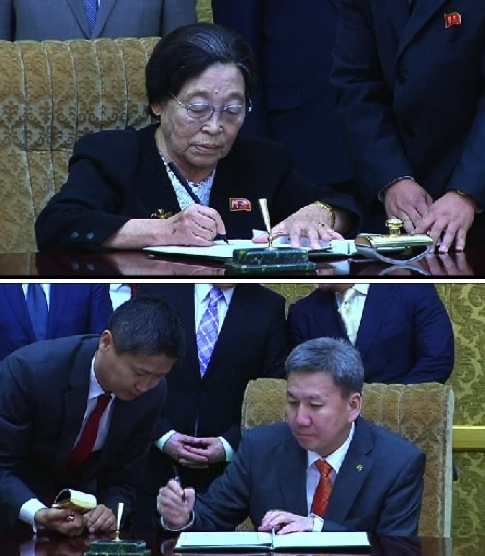 Chair of the Korean Committee for Cultural Relations with Foreign Countries Kim Jong Suk and Mongolian Minister of Foreign Affairs and Trade Luvsanvandan Bold sign an agreement on sports and cultural exchanges and tourism in Pyongyang on 28 October 2013 (Photos: KCNA screen grabs).