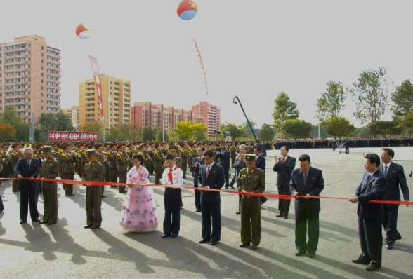 Senor DPRK officials hold a ceremonial red ribbon being cut by representatives of Pyongyang's population during a ceremony opening the Munsu Water Park in east Pyongyang on 15 October 2013 (Photo: Rodong Sinmun).