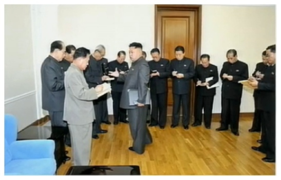 Kim Jong Un talks to senior KWP and DPRK Government officials after an 8 December 2012 expanded meeting of the KWP Political Bureau (Photo: KCTV screen grab).