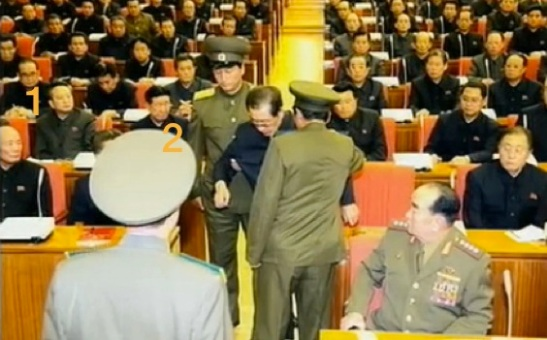 Senior DPRK officials observe Jang's removal from the 8 December 2013 meeting: Joint Venture and Investment Commission Vice Chairman and Senior Deputy Director of the KWP Organization Guidance Department Ri Chol (1) and Deputy Director of the KWP Organization Guidance Department Hwang Pyong So (2) (Photo: KCTV screen grab).