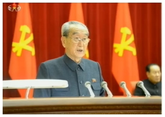 "KWP Secretary and Director of the Propaganda and Agitation Department Kim Ki Nam reads an official report on Jang Song Taek's ""anti-party counterrevolutionary factional acts"" (Photo: KCTV screen grab)."