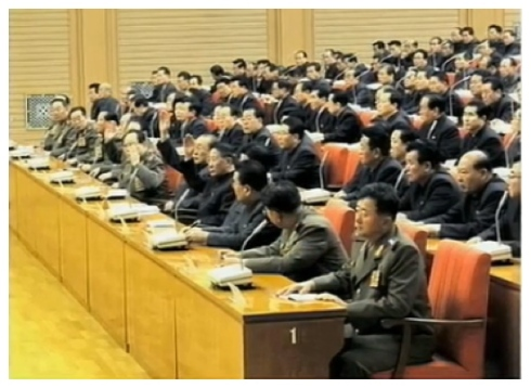 KWP Political Bureau members raise their hands during an expanded meeting held in Pyongyang on 8 December 2013.  Among those in attendance are Ministry of State Security Political Bureau Director Col. Gen. Kim Chang Sop, KWP Civil Defense Department and NDC Vice Chairman VMar Kim Yong Chun, SPA Presidium Vice President Yang Hyong Sop, DPRK Vice Premier Kang Sok Ju and Minister of the People's Armed Forces Gen. Jang Jong Nam (Photo: KCTV screen grab).