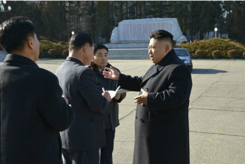 Kim Jong Un talks with DPRK officials in front of an autograph monument at Pyongyang Weak Current Apparatus Factory (Photo: Rodong Sinmun).