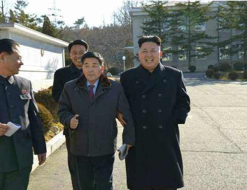 Kim Jong Un links arms with a manger at the Pyongyang Weak Current Apparatus Factory (Photo: Rodong Sinmun).