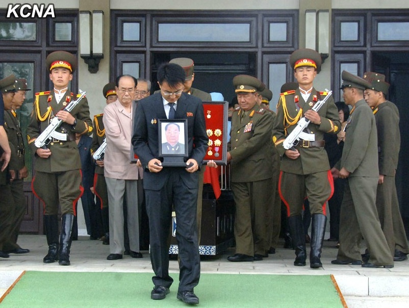 Jon Pyong Ho's grandson bearing a photo of Jon whilst members of the national funeral committee escort Jon's casket from the Sojang Club in Pyongyang on 10 July 2014 (Photo: KCNA).
