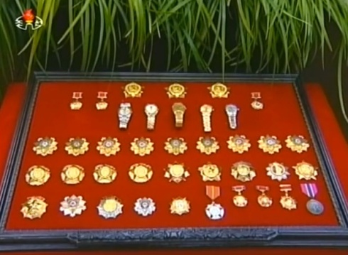 Jon Pyong Ho's state awards, titles and commemorative watches displayed at the foot of his casket (Photo: KCTV).