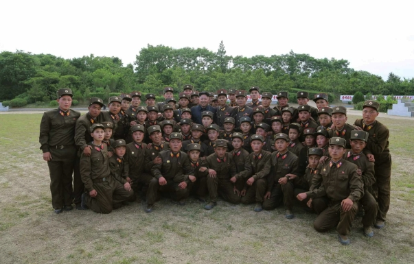 Kim Jong Un poses for a commemorative photo with service members and officers of the Hwa Islet Defense Detachment (Photo: Rodong Sinmun).