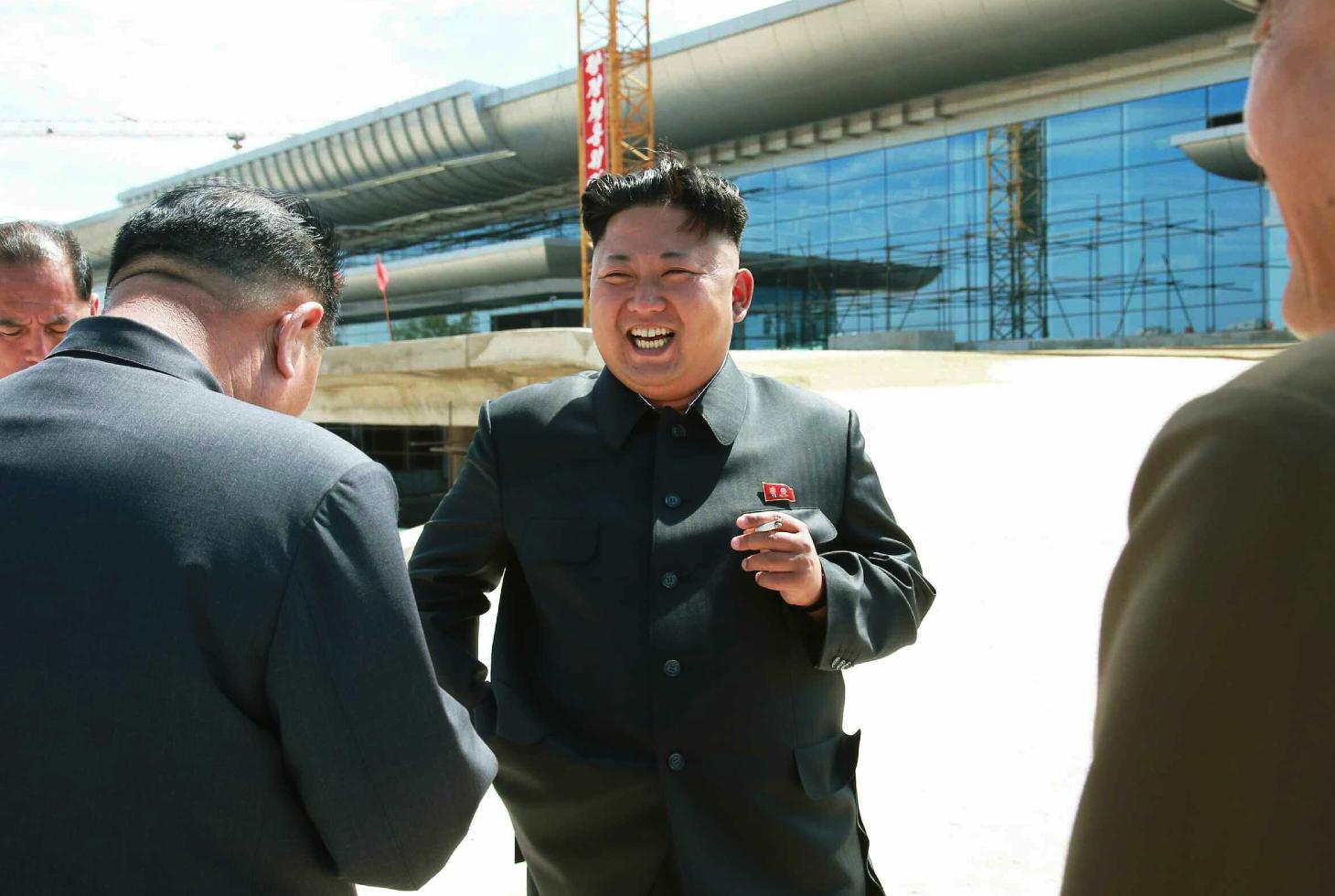 Kim Jong Un smokes a cigarette during his visit to the construction of a terminal at Pyongyang Airport (Photo: Rodong Sinmun).