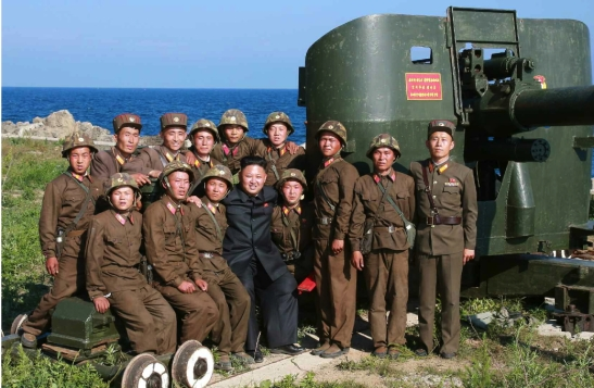 Kim Jong Un poses for a commemorative photo with service members of the Ung Islet Defense Detachment following an artillery training exercise (Photo: Rodong Sinmun).