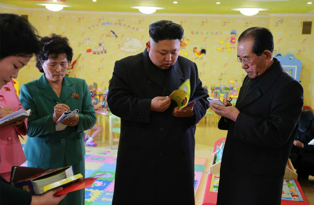 Kim Jong Un leafs through a children's book during a visit to the Pyongyang Baby Home and Orphanage on January 1, 2015.  Also in attendance is Ri Ch'ae-il (right), senior deputy director of the WPK Propaganda and Agitation Department (Photo: Rodong Sinmun).