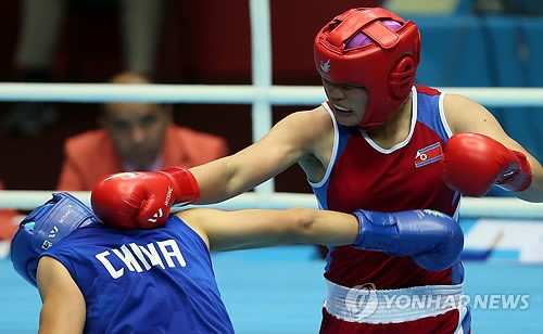 One of the DPRK's 11 gold medallists,  Jang Un Hui (right) connects to PRC's Li Qian during the women's middleweight boxing finals on October 1, 2014 at the 17th Asian Games in Incheon, ROK (Photo: Yonhap).