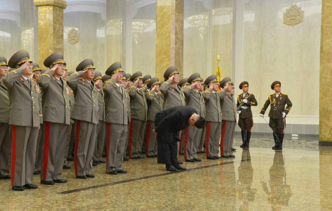 Kim Jong Un bows whilst senior Korean People's Army officials salute in front of statues of Kim Il Sung and Kim Jong Il at Ku'msusan Palace of the Sun in Pyongyang at midnight on February 16, 2015 (Photo: Rodong Sinmun).