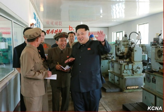 Kim Jong Un tours the Sinu'iju Measuring Instruments Factory. Also in attendance are WPK Secretary Kim Chun Sam (a.) and Second Economy Commission Chairman Jo Chun Ryong (b.) (Photo: KCNA).