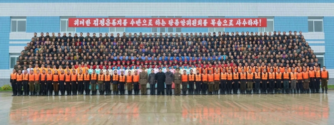 Kim Jong Un poses for a commemorative photograph with managers and employees of the August 25 Fishery Station (Photo: Rodong Sinmun).