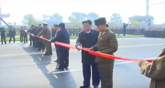 State Planning Commission Chairman and DPRK Vice Premier Ro Tu Chol (a) and a KPA construction service member cut a ceremonial red tape to open the street (Photo: KCTV).