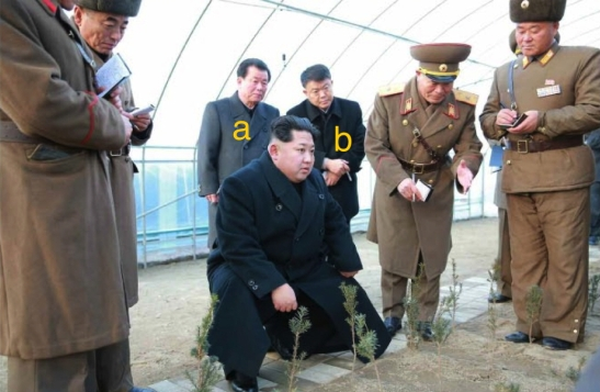 Kim Jong Un is briefed about the cultivation of tree saplings at KPA Tree Nursery #122. Also in attendance are Jo Yong Won [A] and Kim Kyong Jun [B] (Photo: Rodong Sinmun).