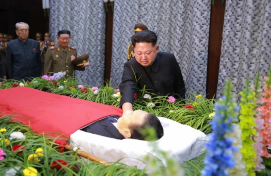 Kim Jong Un touches the embalmed body of WPK Secretary Kim Yang Gon, whilst attending a viewing and wake in Pyongyang on December 30, 2015.  Also seen in attendance (left) are Kim Ki Nam and VMar Hwang Pyong So (Photo: KCNA/Rodong Sinmun).