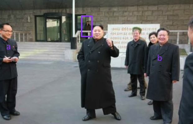 Kim Jong Un outside the Kumkop General Foodstuff Factory for athletes. Also in attendance are WPK Organization Guidance Department deputy director Jo Yong Won (a) and WPK Secretary for Workers' and Social Organizations Choe Ryong Hae (b). In the background of the photo, annotated, is a member of Kim Jong Un's personal security escort (bodyguards) (Photo: Rodong Sinmun/KCNA).
