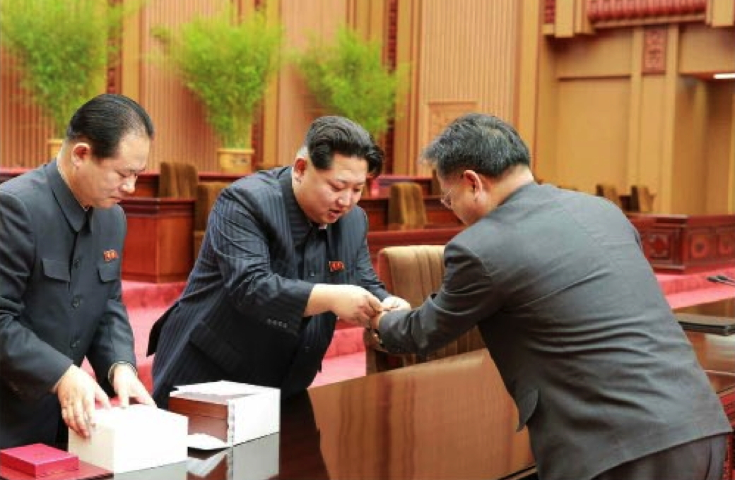 Kim Jong Un presents an award to a DPRK space scientist in Pyongyang on February 17, 2016.  Also in attendance (left) is Hyon Yong Chil, deputy director of the WPK Machine-Building Industry (defense industry) Department (Photo: Rodong Sinmun).