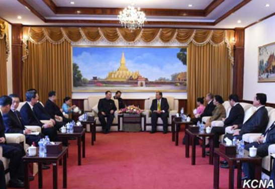 Kim Yong Chol (background, left) meets with Lao People's Revolutionary Party General-Secretary