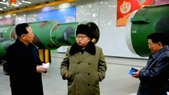 Kim Jong Un is briefed by Hong Su'ng-mu during a meeting with nuclear weapons personnel. The event most likely took place at the T'aeso'ng (Tae-sung) Machine Factory (Photo: KCTV screen grab).