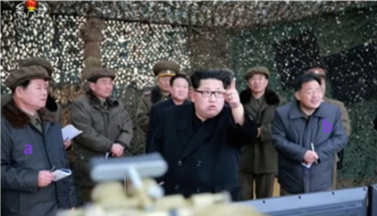 Kim Jong Un points out a projectile fired from an MLRS during test firing.  Also in attendance are WPK Machine-Building Industry (Military Industry) Department Deputy Director Hong Yong Chil [a] and WPK Machine-Building Industry (Military Industry) Deputy Director Kim Jong Sik [b] (Photo: KCTV screen grab).