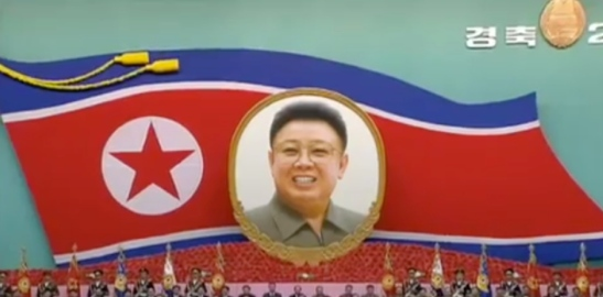 View of a DPRK flag and a graphic of late DPRK leader Kim Jong Il behind the platform at the People's Palace of Culture in central Pyongyang on April 8, 2016 (Photo: KCTV screen grab).