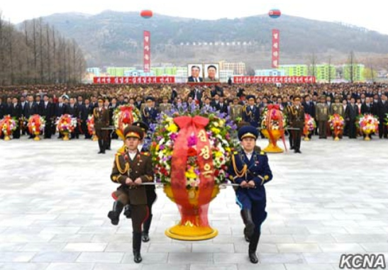 An honor guard representing the KPA's service branches carries a floral basket from Kim Jong Un to the foot of the statues on April 12, 2016 in So'ngch'o'n, South P'yo'ngan Province (Photo: KCNA).