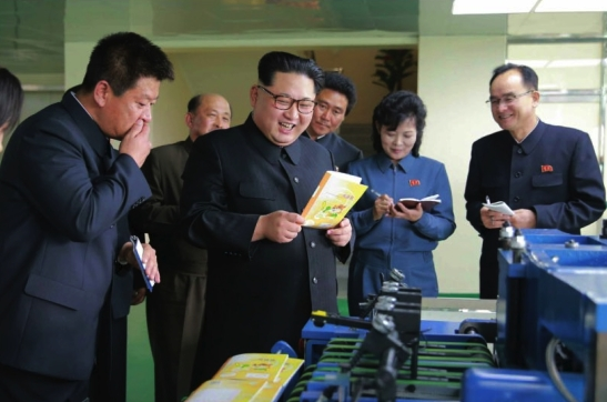 Kim Jong Un inspects a notebook and other products of the Mindulle Notebook Factory (Photo: Rodong Sinmun).