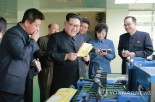Kim Jong Un inspects a notebook and other products of the Mindulle Notebook Factory (Photo: KCNA-Yonhap).