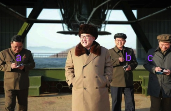 Kim Jong Un at the engine test site at Sohae Space Center.  Also in attendance are WPK Military Industry Department deputy director Kim Jong Sik [a], WPK Military Industry Department Director Ri Man Gon [b] and WPK Military Industry Department deputy director Hong Yong Chil [c] (Photo: Rodong Sinmun).