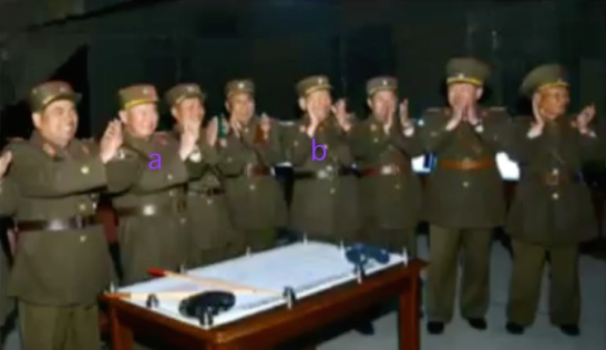 Chief of the KPA General Staff General Ri Myong Su [a] and KPA General Political Director Vice Marshal Hwang Pyong So [b] and members of the KPA high command applaud during a live fire anti-landing artillery drill (Photo: KCTV).